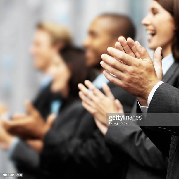 Side profile of a group of young executives clapping (blurred)