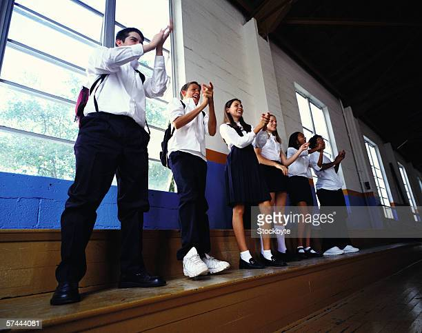 side profile of a group of young students clapping in the sides