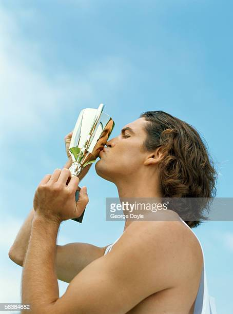 side profile of a male athlete kissing a trophy