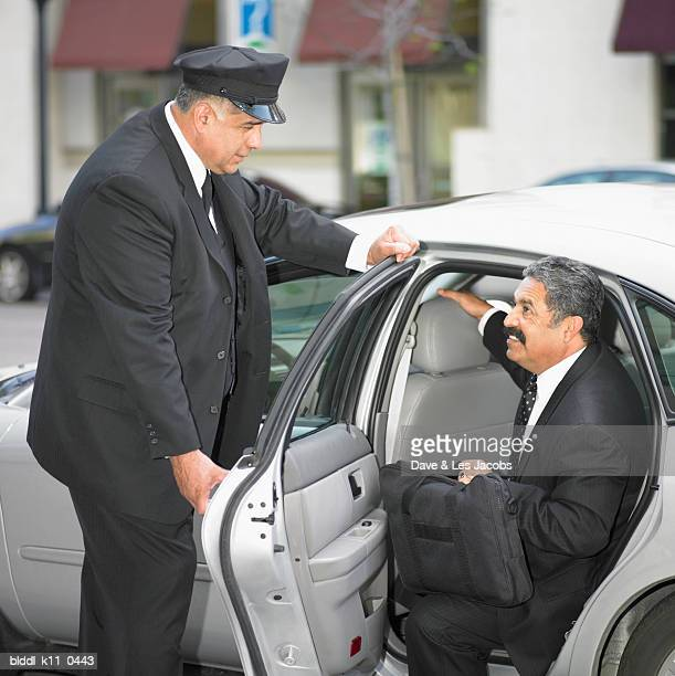 Side profile of a male chauffeur opening the door of a limousine