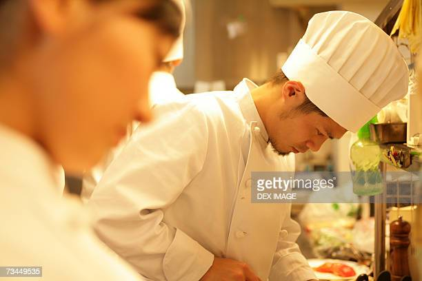 Side profile of a male chef and his colleagues in the kitchen