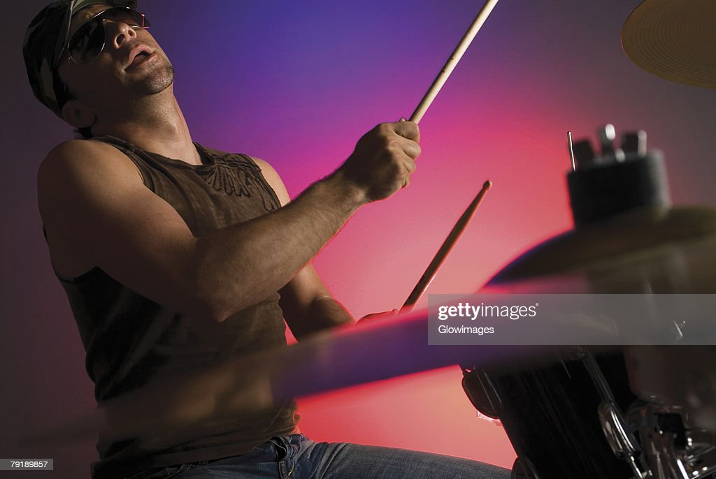 Side profile of a male drummer playing drums : Stock Photo