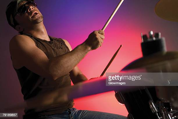 Side profile of a male drummer playing drums