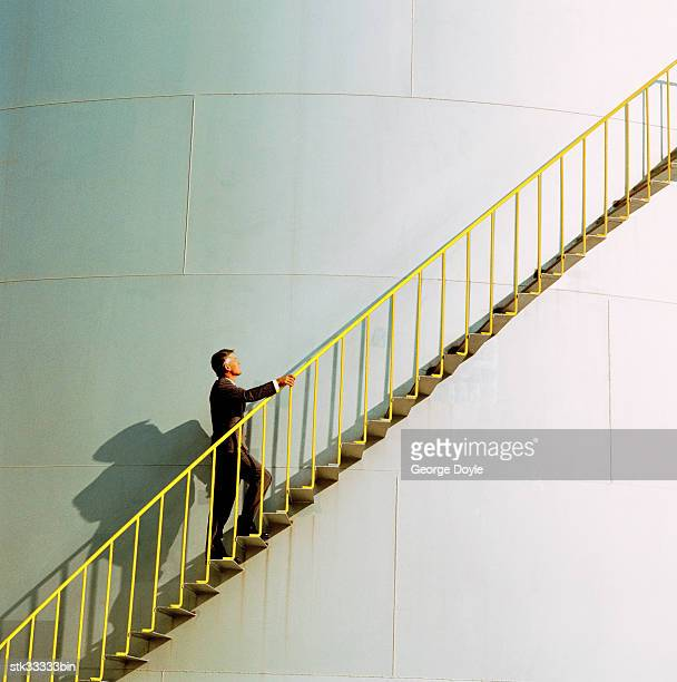 side profile of a man climbing the ladder of an industrial silo