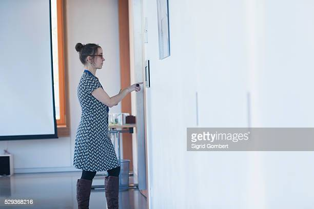 side profile of a mature lecturer operating wall mounted security system in lecture hall, freiburg im breisgau, baden-w��rttemberg, germany - sigrid gombert stock-fotos und bilder