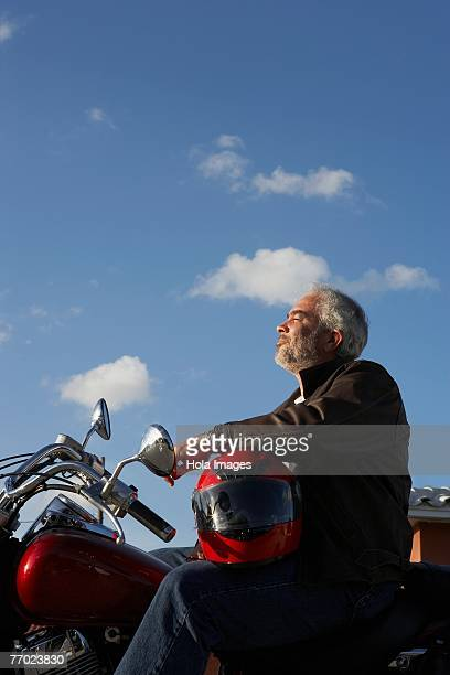Side profile of a mature man sitting on a motorcycle
