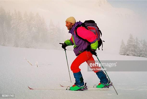 Side profile of a mature man skiing on snow, Petros Mountain, Carpathian Mountain Range, Ukraine
