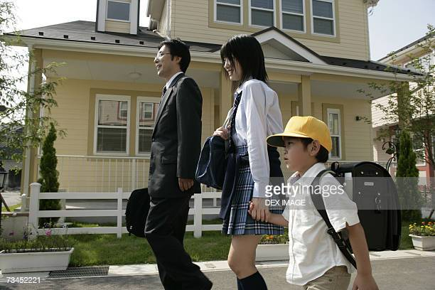 Side profile of a mature man walking with his son and daughter on the road