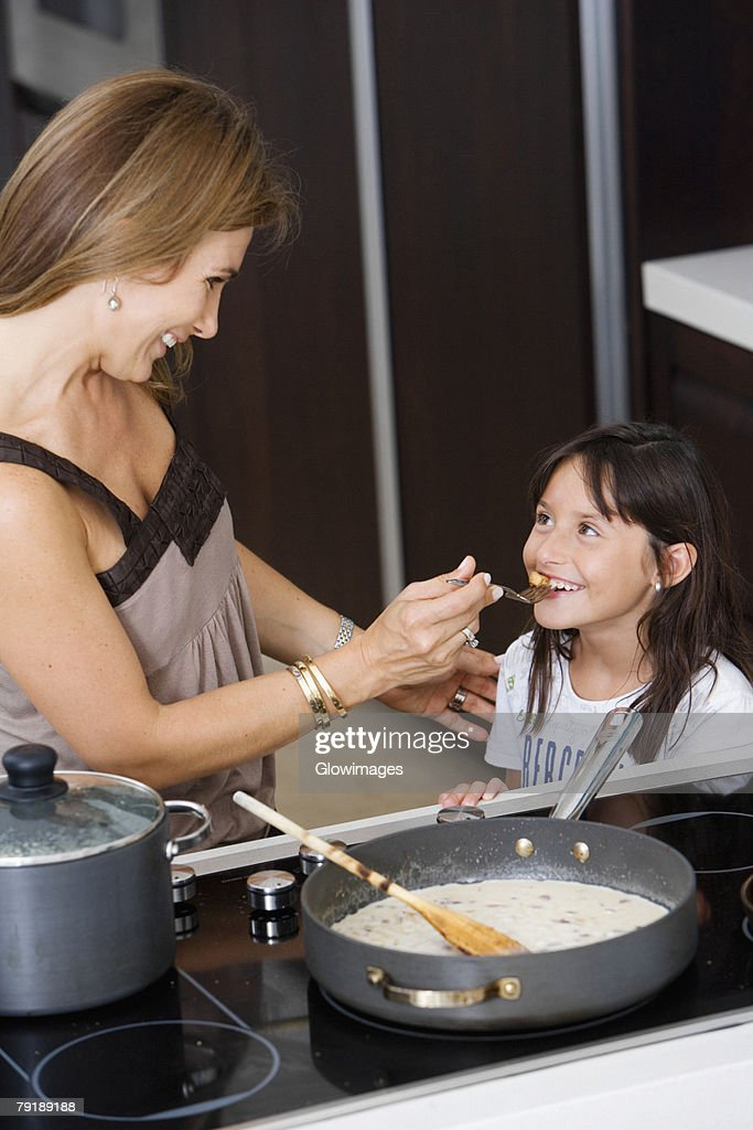 Side profile of a mature woman feeding food to her daughter : Foto de stock