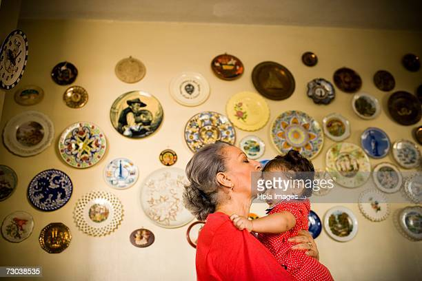 side profile of a mature woman holding her granddaughter - dominican ethnicity stock photos and pictures