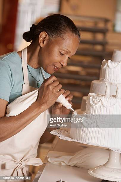 side profile of a mature woman icing a cake - decorating a cake stock pictures, royalty-free photos & images