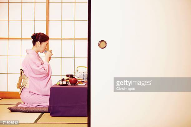 Side profile of a mature woman wearing a Kimono and drinking from a cup