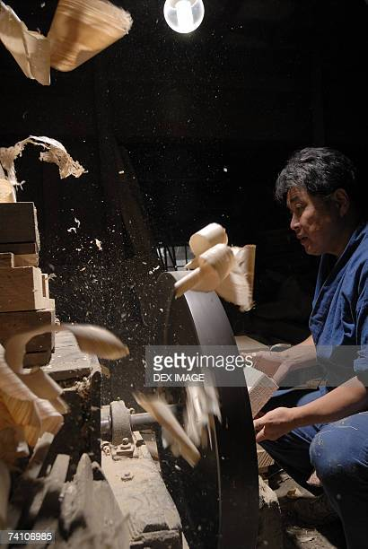 Side profile of a mid adult man cutting wood in a workshop