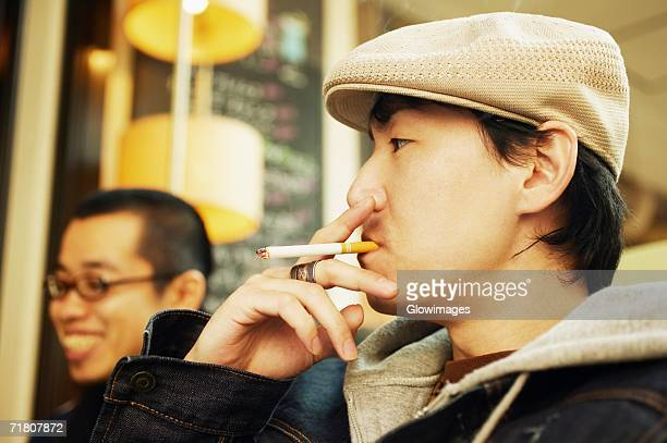 Side profile of a mid adult man smoking a cigarette and a young man smiling beside him