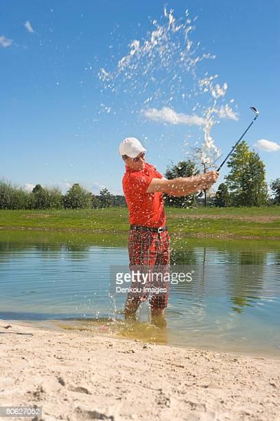 Side profile of a mid adult man swinging a golf club in waterhole in a golf course