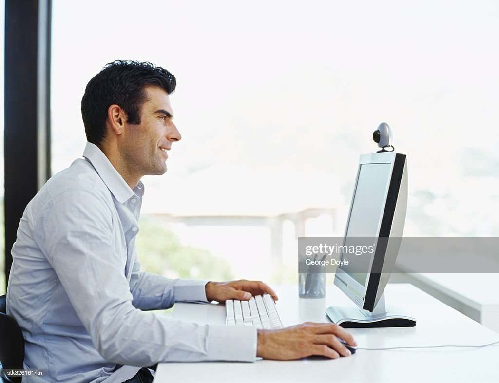 side profile of a mid adult man using a computer : Stock Photo