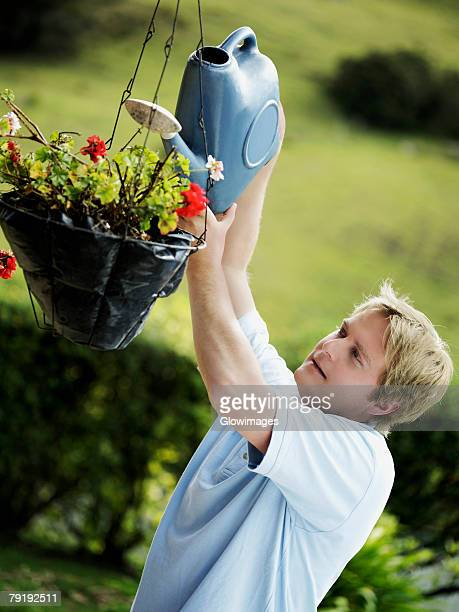 side profile of a mid adult man watering a potted plant - hanging basket stock pictures, royalty-free photos & images