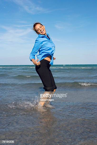 side profile of a mid adult woman dancing on the beach - rolled up pants stock pictures, royalty-free photos & images