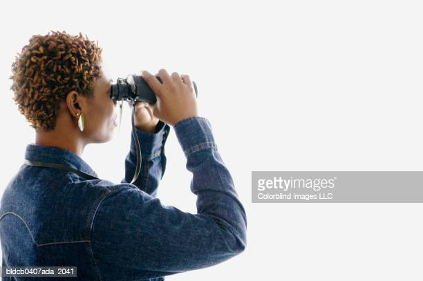 Side profile of a mid adult woman looking through binoculars