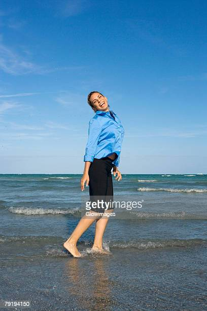 side profile of a mid adult woman standing on the beach - rolled up trousers stock pictures, royalty-free photos & images