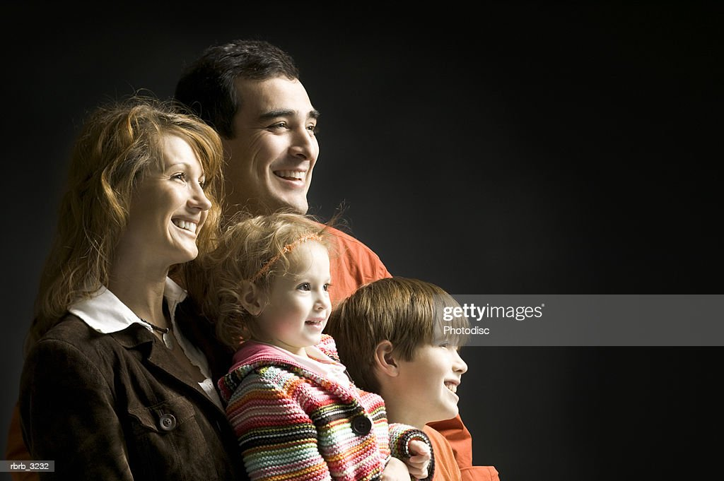 Side profile of a mother and father with their two children : Foto de stock