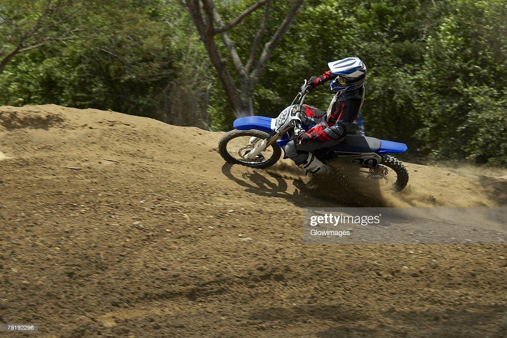 Side profile of a motocross rider riding a motorcycle : Foto de stock