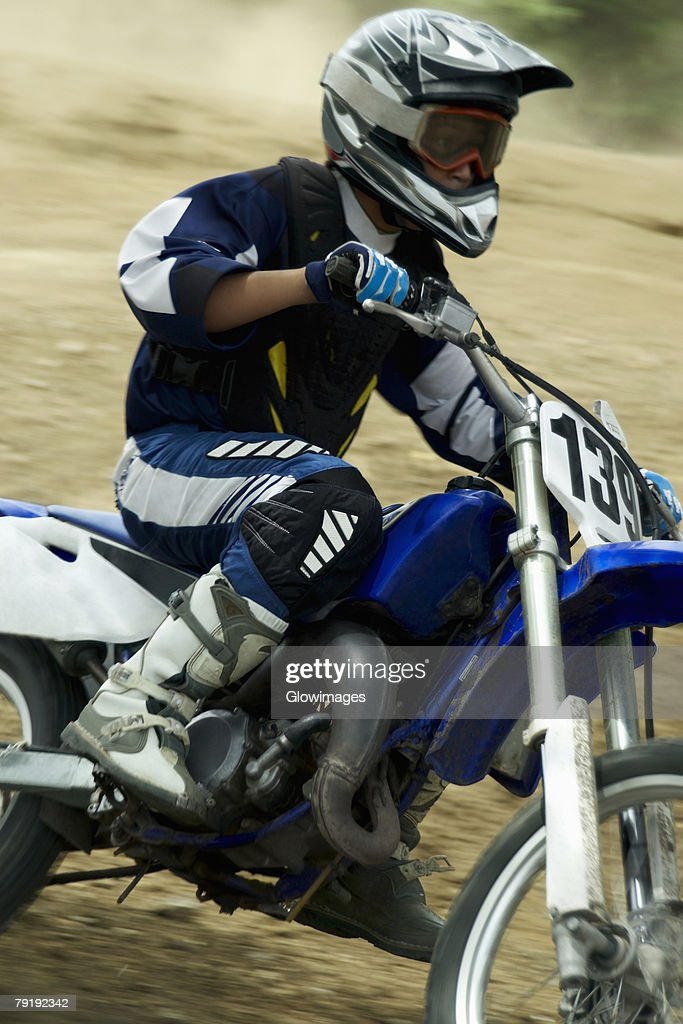 Side profile of a motocross rider riding a motorcycle : Foto de stock
