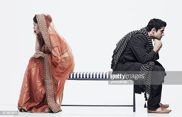 Side profile of a newlywed couple sitting on opposite ends of a bench