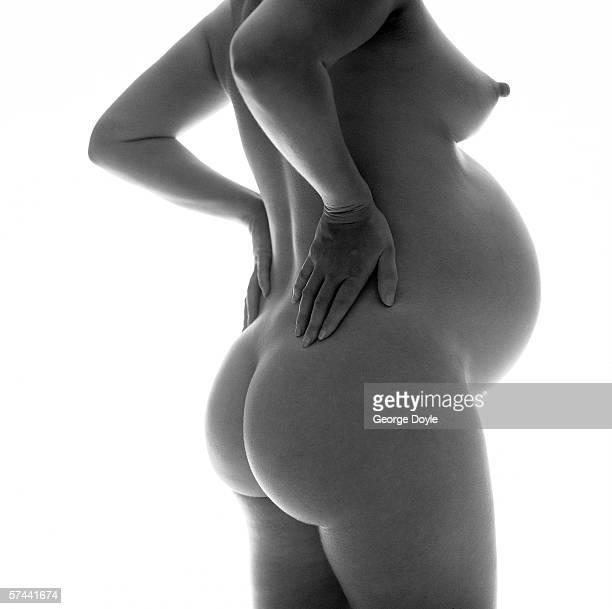 side profile of a nude pregnant woman - weibliche brust schwanger stock-fotos und bilder