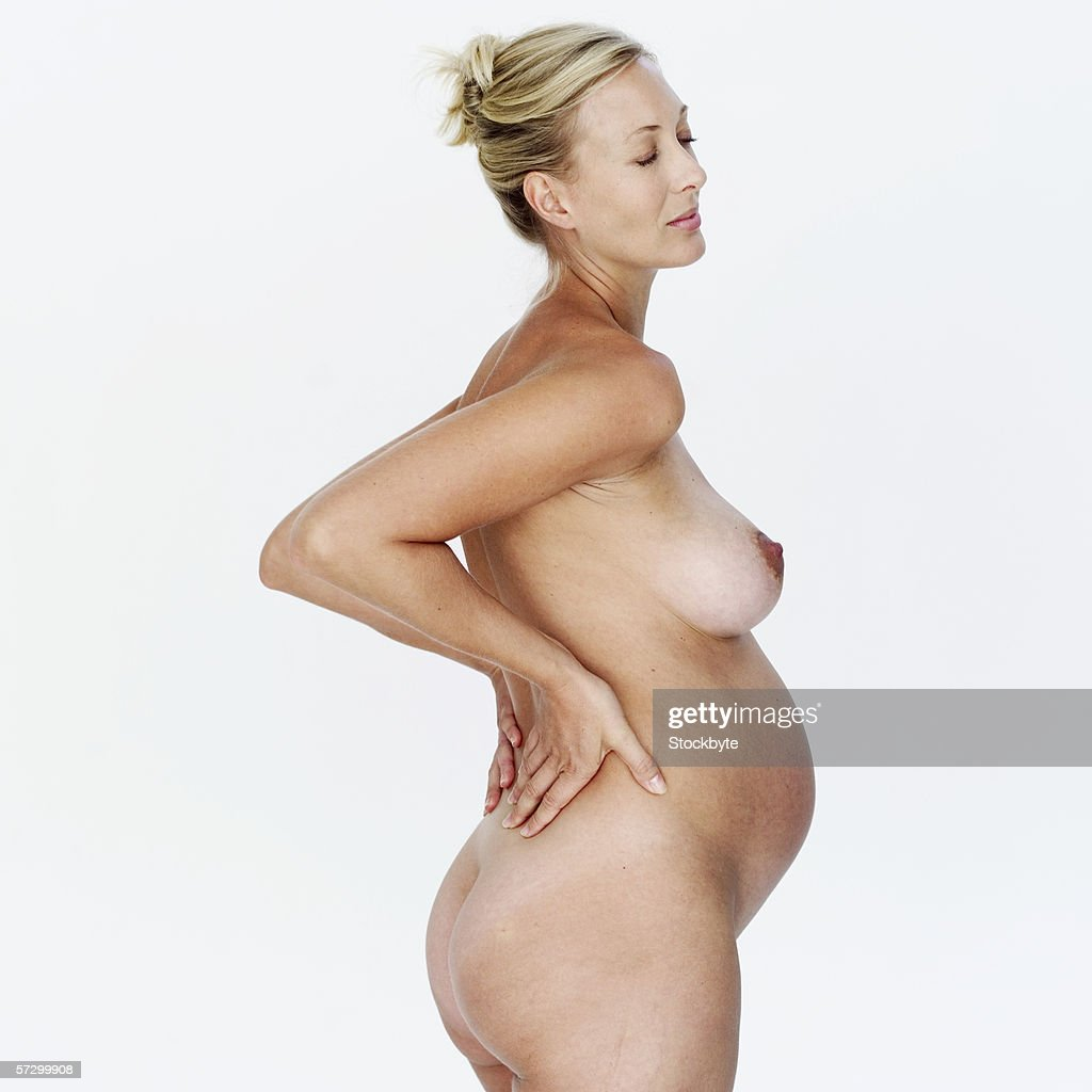 side profile of a nude pregnant woman with her hands on her back