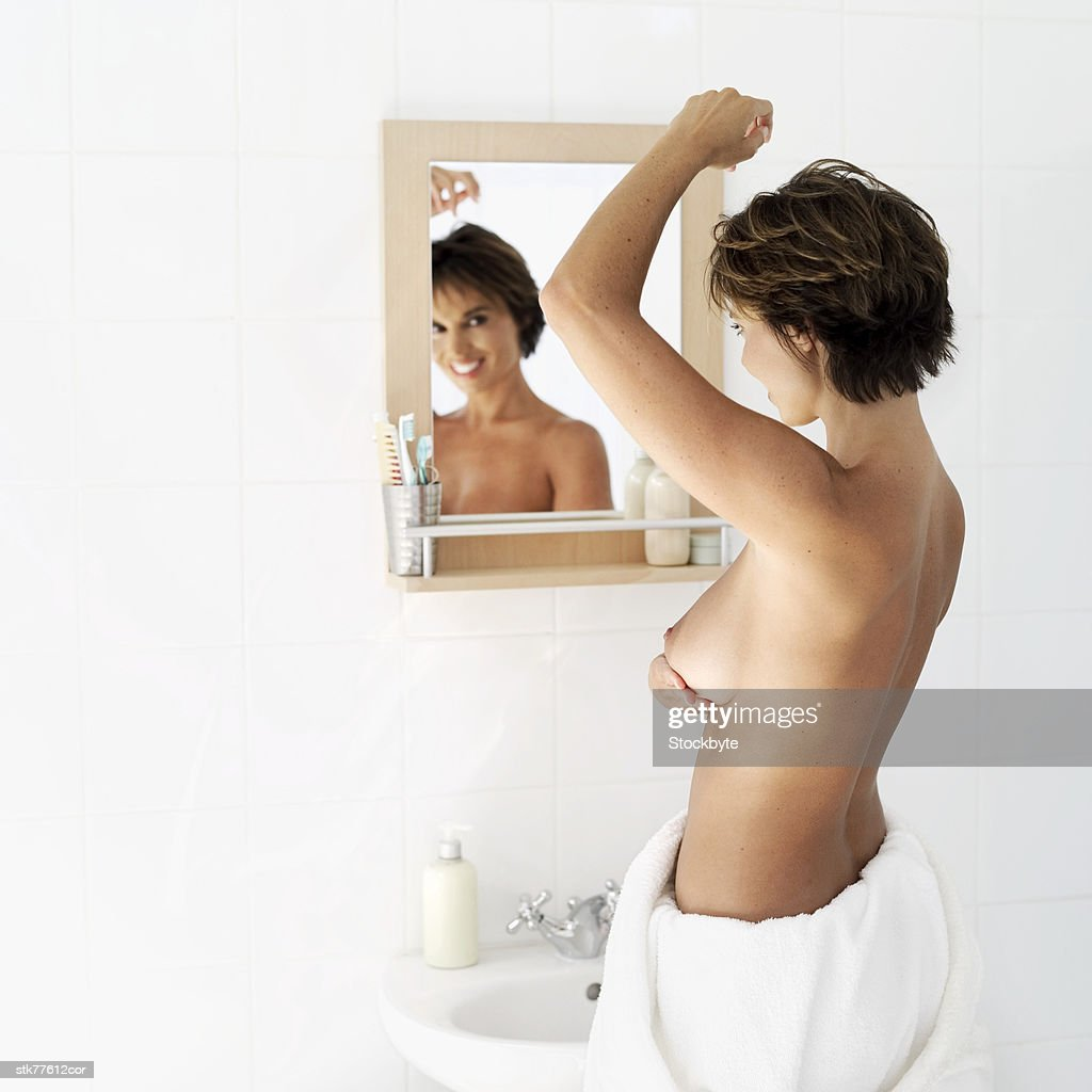 side profile of a nude woman looking in a mirror and touching her