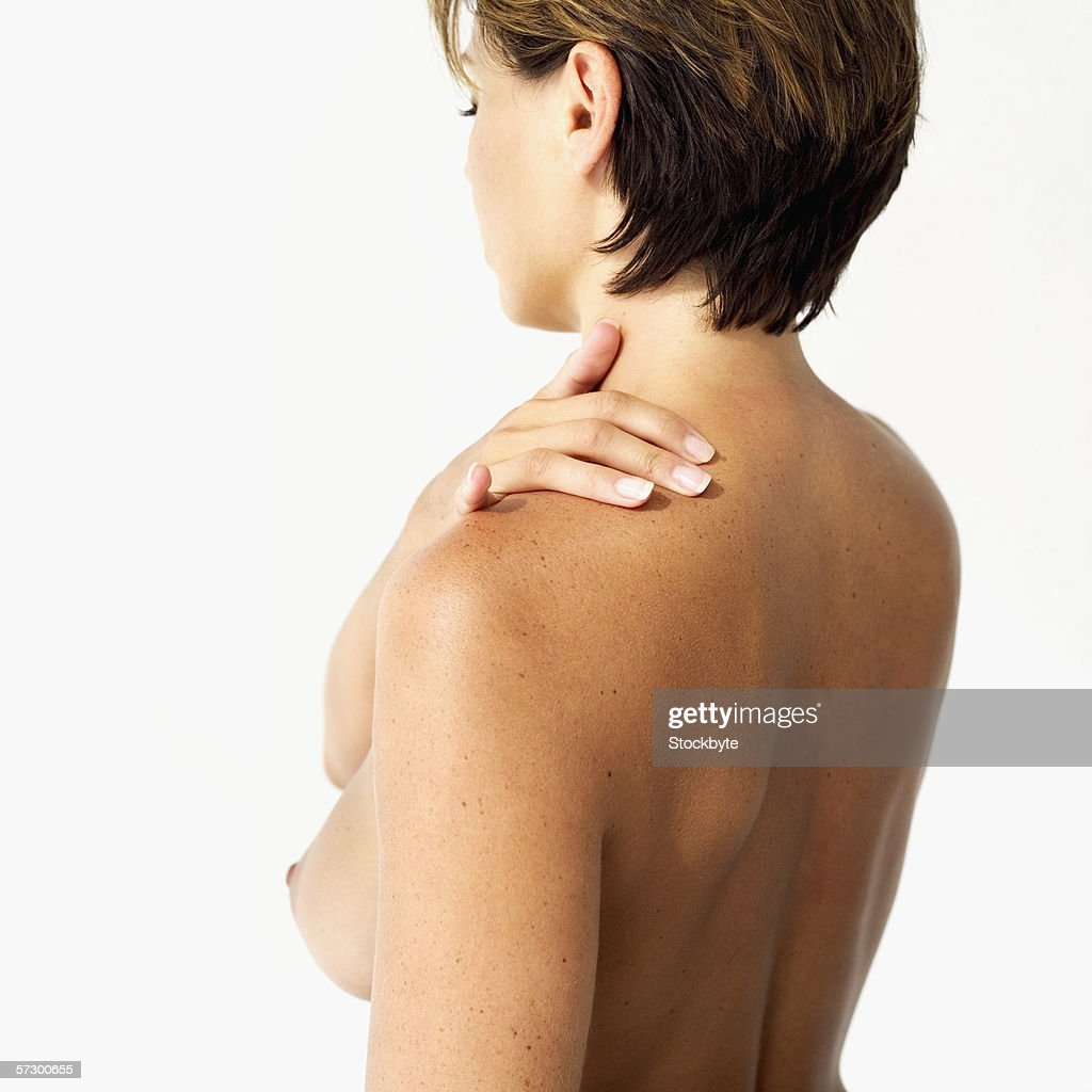 side profile of a nude young woman standing with her hand on her