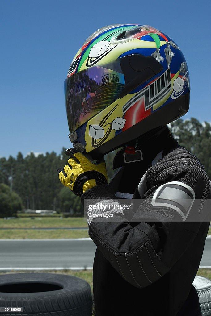 Side profile of a person adjusting his crash helmet : Foto de stock