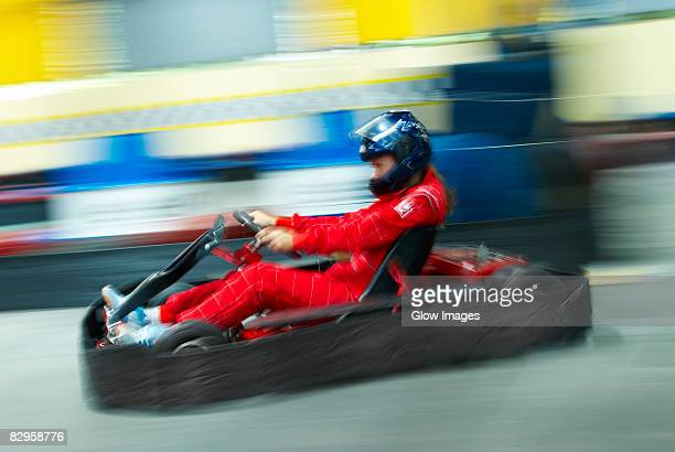 Side profile of a person go-carting on a motor racing track