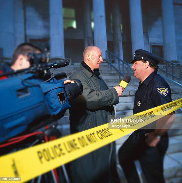 side profile of a reporter questioning a police officer at a crime scene