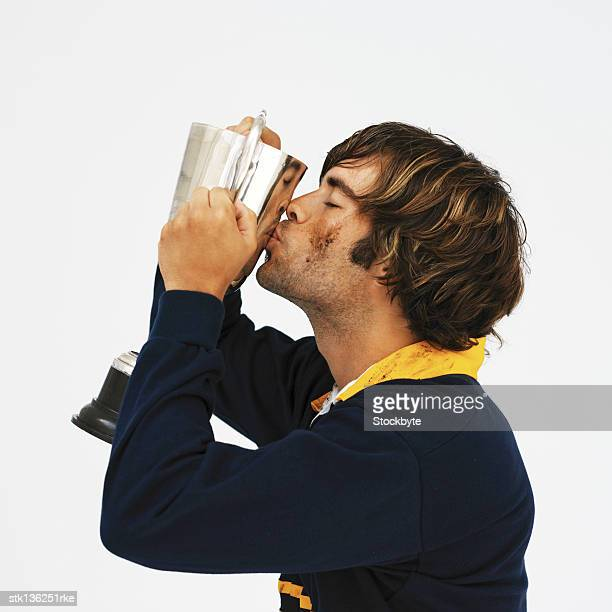 side profile of a rugby player kissing a trophy