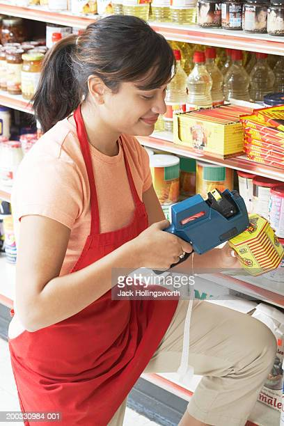 side profile of a saleswoman decoding the price of a grocery item with a bar code reader - labeling stock pictures, royalty-free photos & images