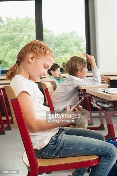 side profile of a schoolgirl using a smart phone in classroom, munich, bavaria, germany - kurdish girl stock photos and pictures