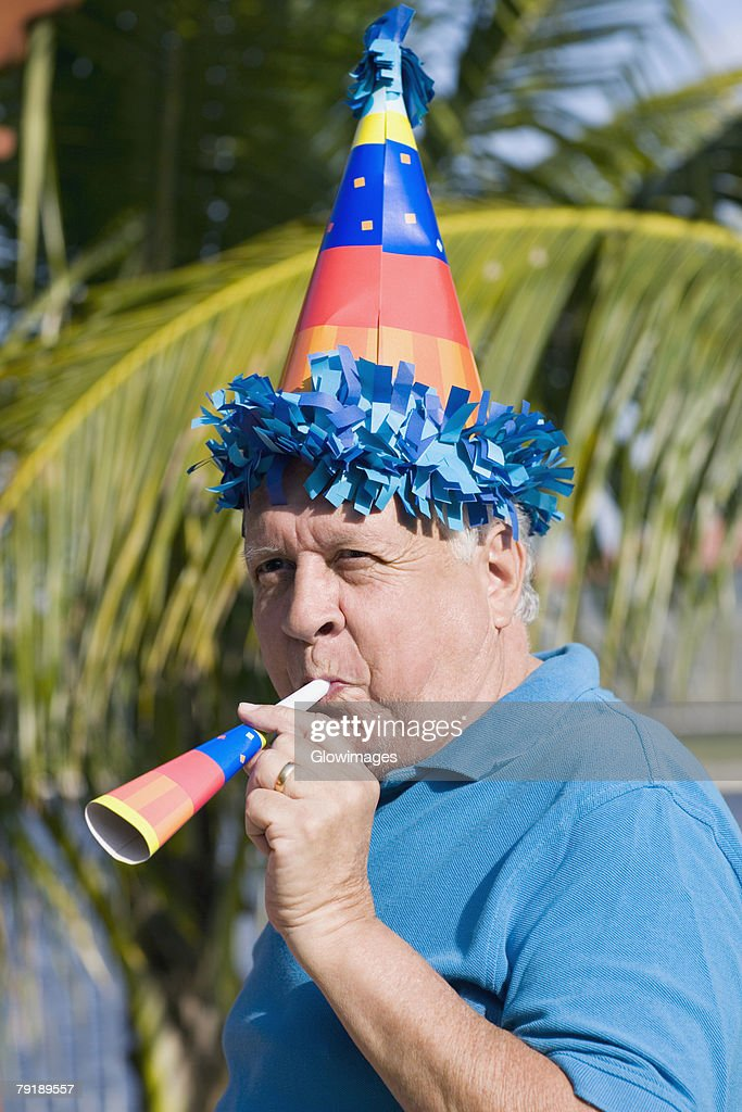 Side profile of a senior man blowing a party horn blower : Stock Photo