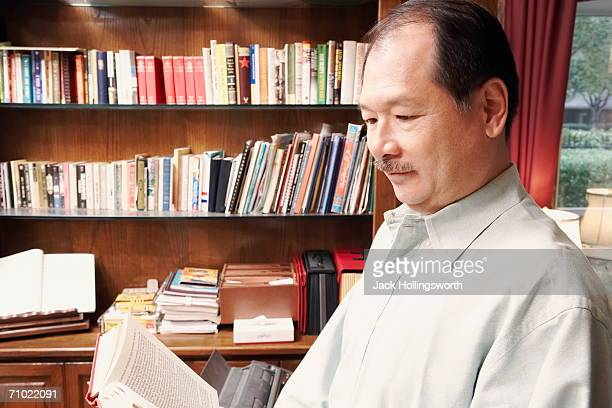 Side profile of a senior man reading a book