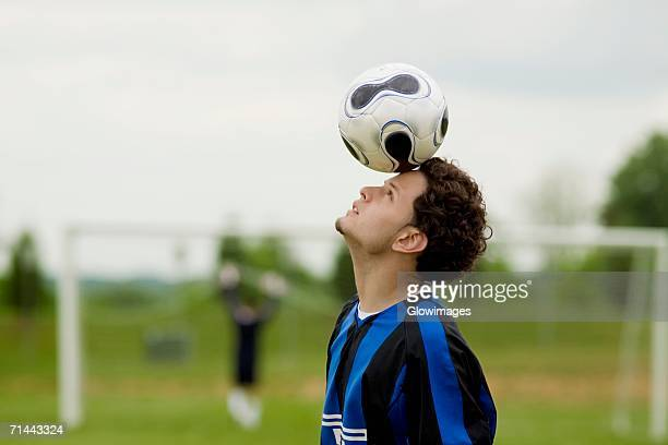 Side profile of a soccer player balancing a soccer ball on his forehead