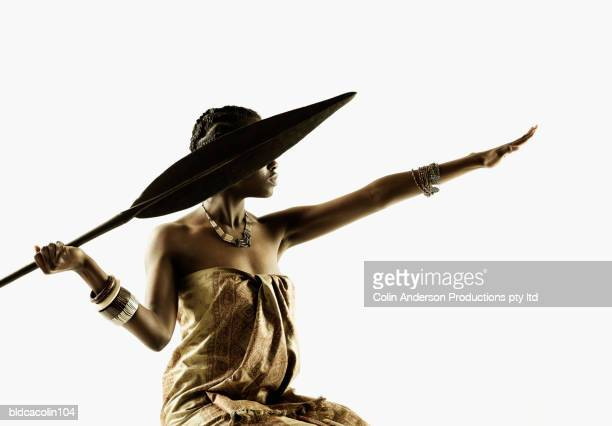 side profile of a tribal young woman throwing a spear - spear stock photos and pictures