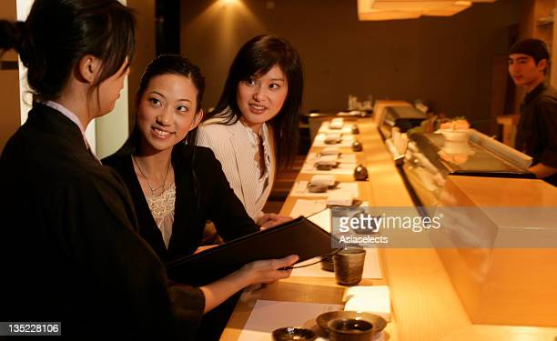 Side profile of a waitress showing a menu card to a businesswoman