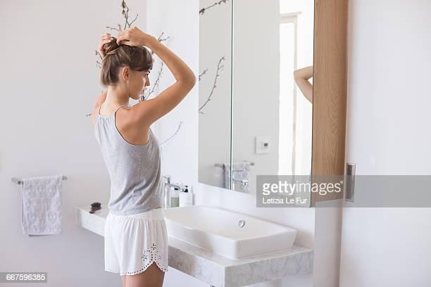 side profile of a woman adjusting her hair in a bathroom - opgestoken haar stockfoto's en -beelden