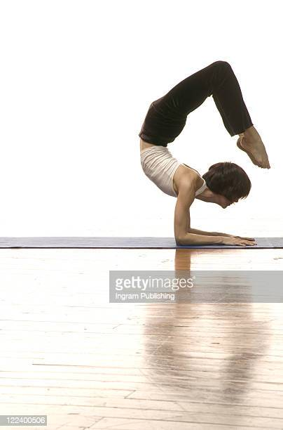 Side profile of a woman doing handstand