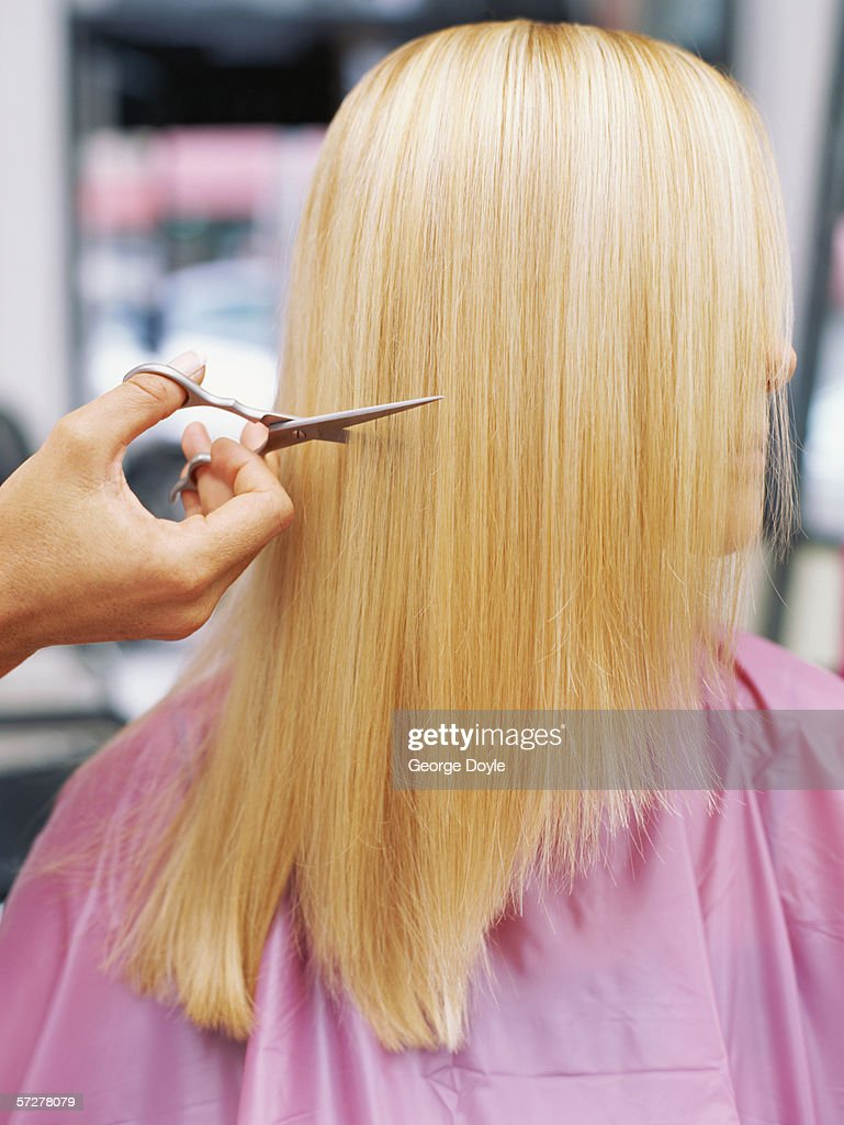 Side profile of a woman having her hair done : Stock Photo