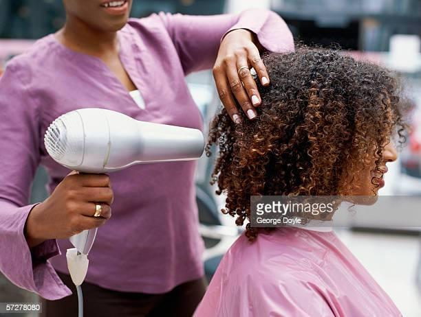 side profile of a woman having her hair dried with a hair dryer - rizado peinado fotografías e imágenes de stock