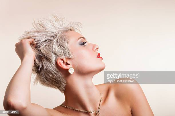 Side profile of a woman holding her blonde hair