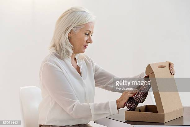 Side profile of a woman opening a parcel of sandal