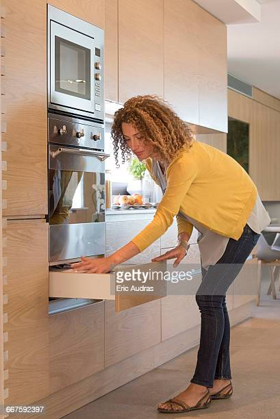 Side profile of a woman opening drawer